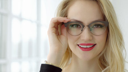 Close up of a young beautiful woman with glasses at the window and looking at camera, selective focus