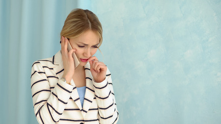 Young alarmed woman in a striped jacket talking on the phone.