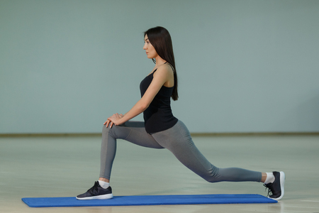 Young attractive smiling woman practicing yoga on the mat at home,copyspace