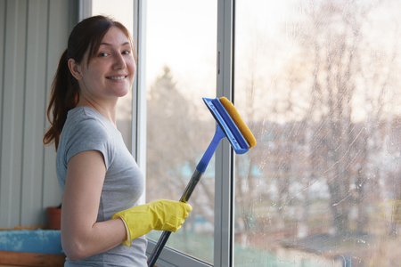 Young woman in yellow gloves washing the window of a special mop and looking at camera.