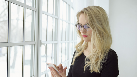 Portrait of a young blonde woman in glasses with a phone at the big window. 写真素材 - 103403442