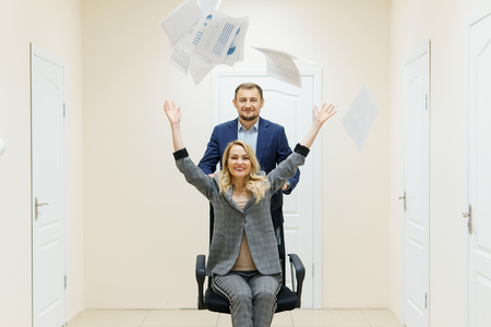 Business man and woman have fun in the office during a break. People celebrate a successful deal and throwing paper up. Stock fotó