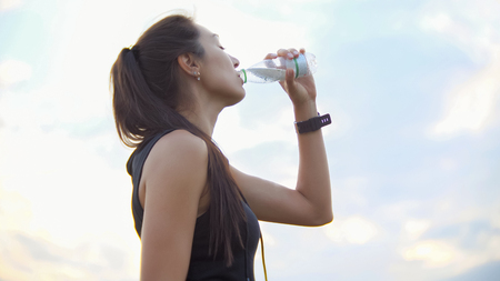 Joven deportista hermosa bebe agua de una botella al aire libre después del entrenamiento