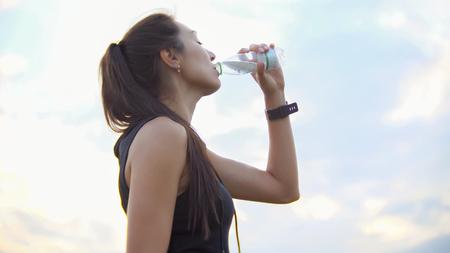 Junge schöne Sportlerin trinkt nach dem Training Wasser aus einer Flasche im Freien