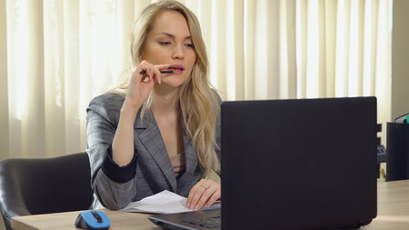 Young business woman in suit works at the computer in office