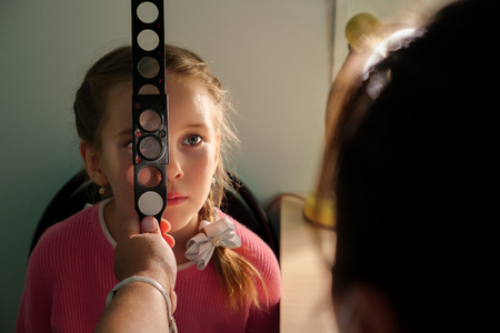 optometry concept - medical doctor with magnifier examining little girl.