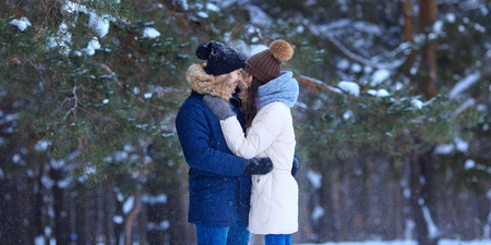 Happy young couple hugs in winter snowy woods. Romantic lifestyle of man and woman in love