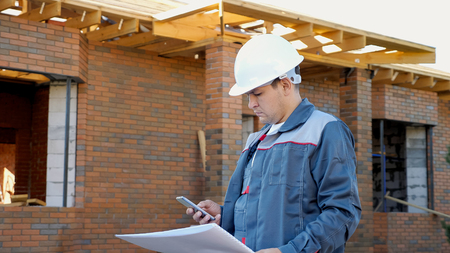 Man in white hardhat and overall holding paper plans of building and using phone outside on site