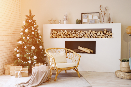 White room with fireplace in the bedroom. Christmas tree decorations, sunlight Standard-Bild