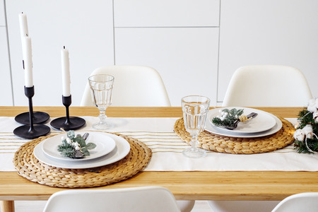 Christmas dinner by candlelight, table setting in in modern kitchen. Imagens