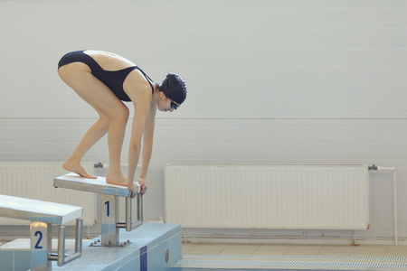 Young female swimmer in low position on starting block in a swimming pool