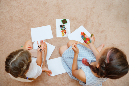 top view of girls drawing with watercolors on paper and on hands sitting on floor