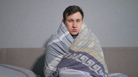 sick man wrapping in warm blanket and shivering with cold. Stockfoto