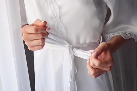 girl ties belt on her robe standing near window. Standard-Bild