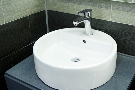 close up of bathroom interior with circle sink and faucet.