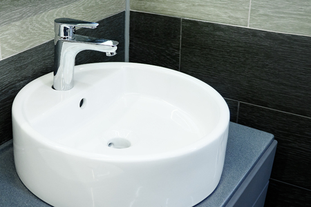 Bathroom interior with circle sink and faucet.