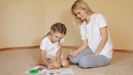 Beautiful woman with girl sitting on floor and drawing on paper with watercolor Stok Fotoğraf