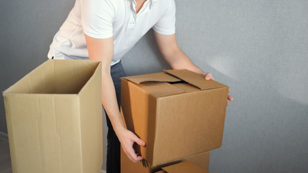 Young delivery service man carrying Boxes Into New Home On Moving Day, copy space Stockfoto