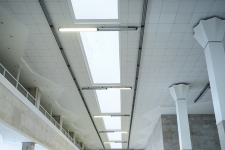 Lights in long line on ceiling of the office industrial building, exhibition hall. Archivio Fotografico