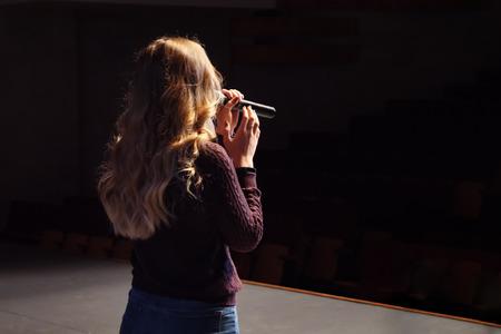 unrecognizable singer on stage. Dark background, spotlights