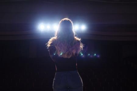cantante irriconoscibile in piedi sul palco al microfono in un night club, vista posteriore Archivio Fotografico