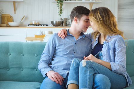 Young couple sitting on sofa and hugging in kitchen, copy space,
