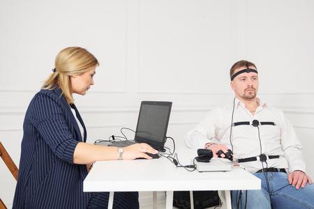 businessman sits for a lie detector examination.