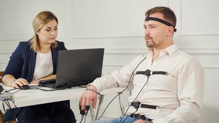 técnico de polígrafo lee preguntas desde una computadora portátil. hombre conectado al circuito detector de mentiras.