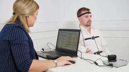 Junger gutaussehender Verdächtiger unterzieht sich während des Verhörs einem Lügendetektor, der mit der Maschine verbunden ist. Standard-Bild