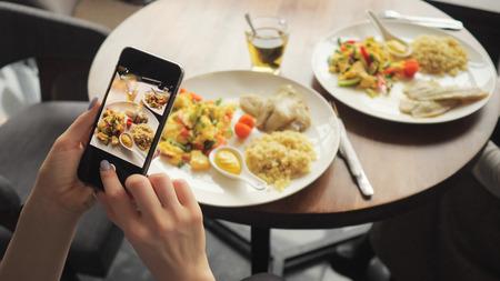 La bloguera toma fotos de su comida en un café usando un teléfono móvil. Manos con primer plano de la pantalla del teléfono.