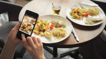 Woman blogger takes photos of her food in a cafe using mobile phone. Hands with phone screen close-up. Banco de Imagens
