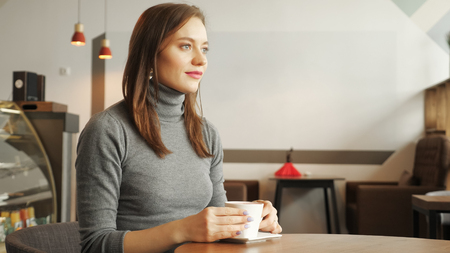 Young women is drinking a cup of coffee sitting in cafe in the city. Side view.