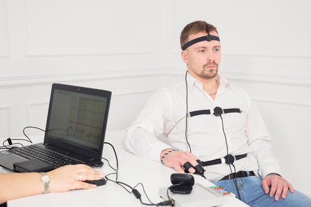 businessman sits for a lie detector examination.