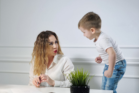 Secretaria joven con su pequeño hijo en el lugar de trabajo en la oficina. El niño requiere que su madre juegue con él golpeando la mesa con el puño. Mamá trabajadora.