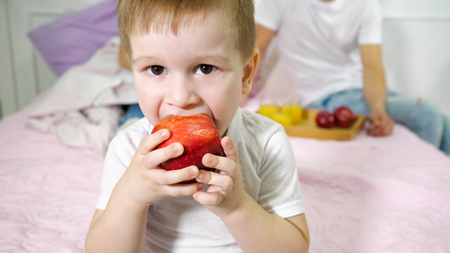 Cute little boy is eating red apple in parents bedroom and looking at camera. His parents sitting on the bed on background. Family weekend at home.
