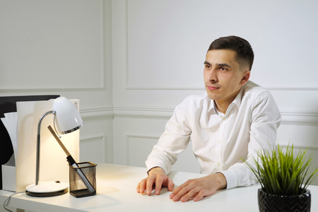 Office worker young man in white shirt is procrastinating sitting at work at the office table. Dreaming about something.