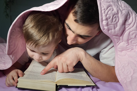 Portrait of dad teaches his little son to read a book hiding under the blanket in bed before bedtime. 版權商用圖片
