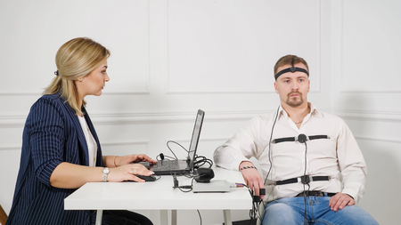 Young Handsome Suspect During Interrogation Undergoes Lie Detector Connected to the Machine He Answers Yer or No Questions.