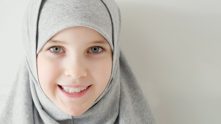 Portrait of young attractive muslim 9-years girl wearing grey hijab and traditional dress looking at the camera and smiling on light background, copy space.