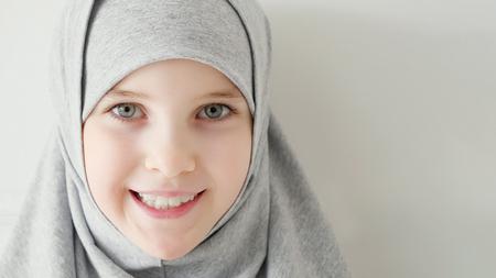 Portret młodej atrakcyjnej 9-letniej muzułmańskiej dziewczyny ubrana w szary hidżab i tradycyjny strój, patrząc w kamerę i uśmiechając się na jasnym tle, miejsce.