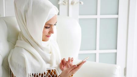 Retrato de joven musulmana con hijab blanco y vestimenta tradicional está navegando por las páginas de Internet en el teléfono inteligente sentado en el sofá, vista lateral. copyspace