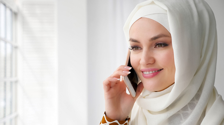 Portrait of attractive muslim woman in white hijab is talking mobile phone and smilng standing near the window, copy space