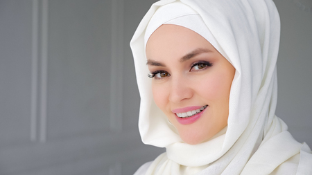Portrait of beautiful young muslim arabian woman wearing white hijab, slowly rising her eyes looking at camera and smiling.