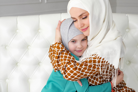 Muslim family mom and her little daughter in hijabs are hugging sitting on the sofa at home in modern white interior, side view.