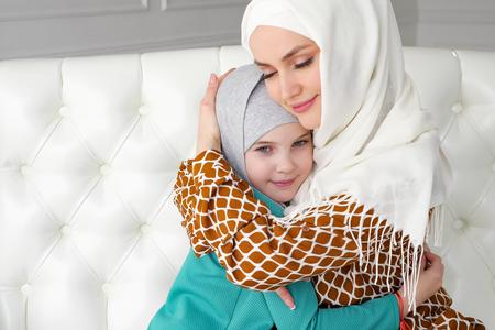 Muslimische Familienmutter und ihre kleine Tochter in Hijabs umarmen sich zu Hause auf dem Sofa im modernen weißen Interieur, Seitenansicht.