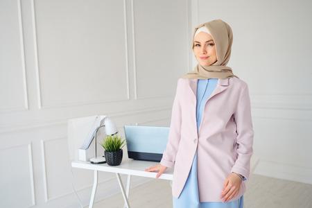 Stilvolle junge muslimische Frau in beigem Hijab und traditioneller Kleidung, die in der Nähe des Arbeitsplatzes steht, Kopienraum.