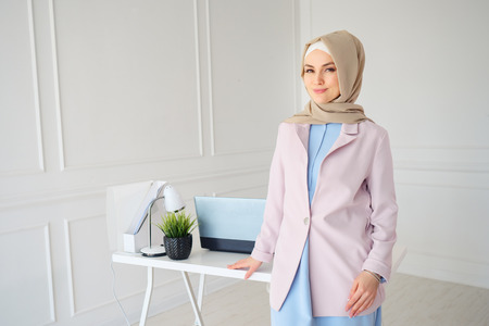 stylish young muslim woman in beige hijab and traditional clothes standing near workplace, copy space.