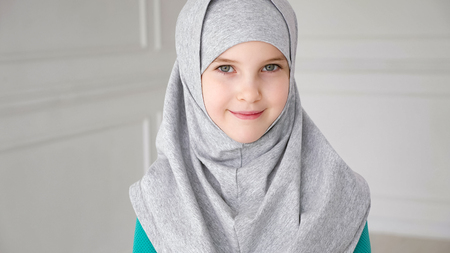 Portrait of muslim 9-years old teen girl in grey hijab is looking in camera and laughing.