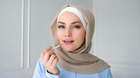 Portrait of young muslim woman in beige hijab and traditional blue dress is applying compact powder with sponge on her face looking at small mirror at home, side view.
