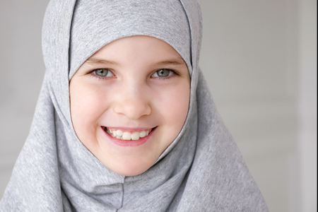 Portrait of young attractive muslim 9-years girl wearing grey hijab and traditional dress looking at the camera and smiling on light background. close-up